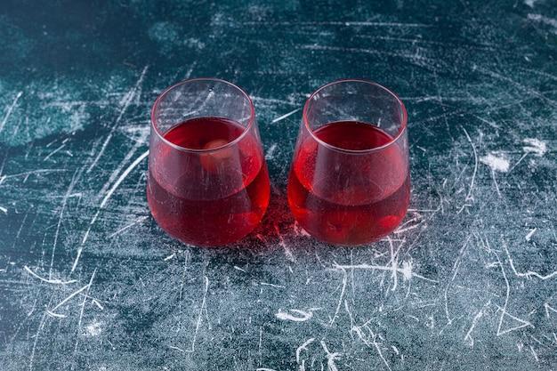 Две стеклянные чашки свежего сока размещены на красочной.