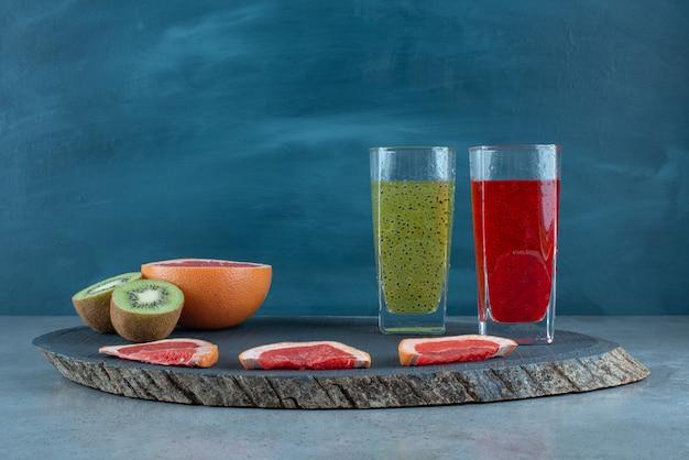 さまざまな果物のスライスとフレッシュジュースの2つのガラスカップ。