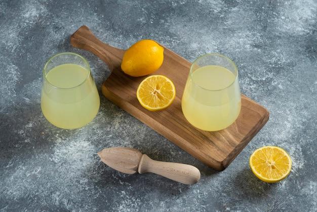 신선한 레몬 주스와 나무 리머의 두 유리 컵.
