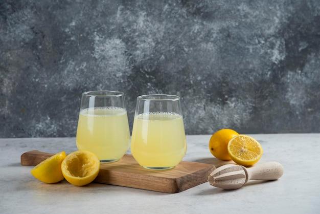 木の板に新鮮なレモンジュースの2つのガラスカップ。