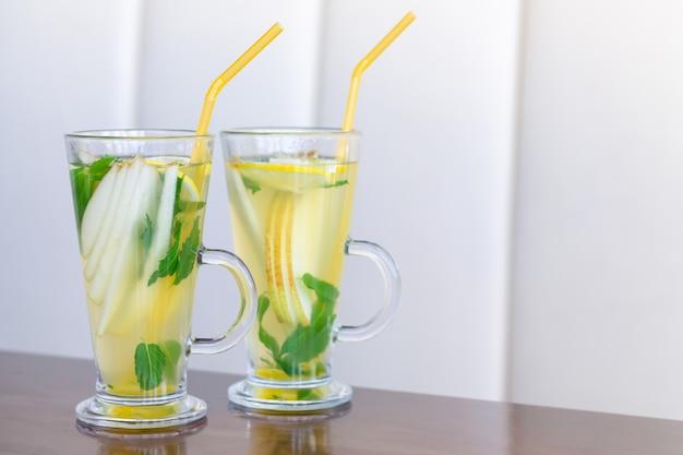 木製のテーブルにミント、レモン、洋ナシ、蜂蜜、生姜とフルーツティーの2つのガラスカップ