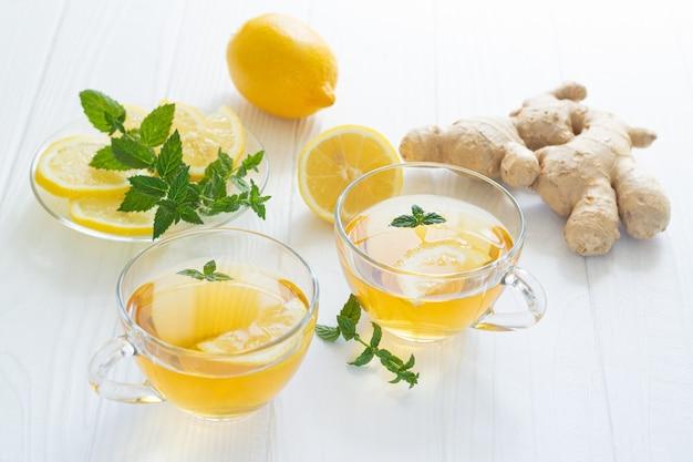 ミントとレモンの白いテーブルの上の健康的なジンジャーティーの2つのガラスのコップ