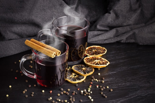 暗いテーブルの上に蒸気をかけたグリューワイン2杯。乾燥した柑橘系の果物と調味料。暗いタオルの表面に対する静物。