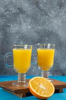 나무 보드에 오렌지 주스의 두 유리 컵.