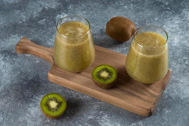 木の板においしいキウイジュースの2つのガラスカップ。