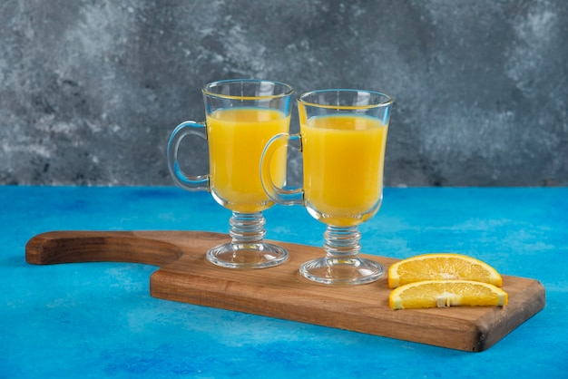 Two glass cups of orange juice on wooden board.