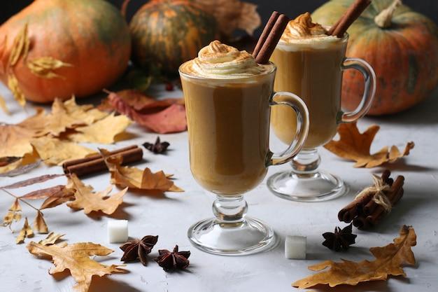 Две стеклянные чашки тыквенного латте со специями на сером столе с тыквами и осенними листьями, крупным планом.