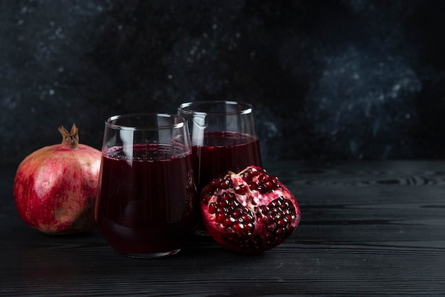 Two glass cups of sweet pomegranate juice on dark.