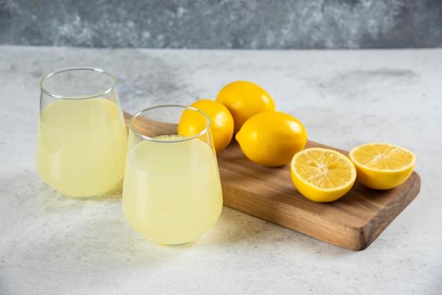 Two glass cups of tasty lemonade on a wooden board.