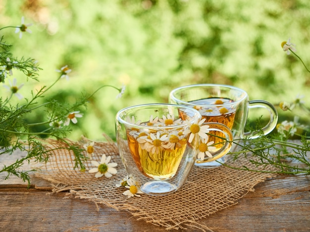 Two glass cups of tea with chamomile on a piece of burlap