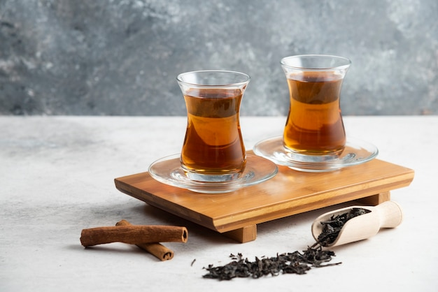 Two glass cups of tea with cinnamon sticks and loose teas.high quality photo