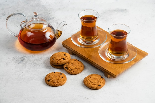 Two glass cups of tea with delicious cookies .