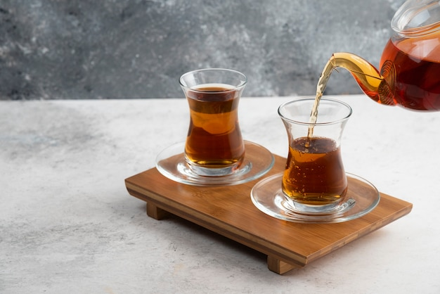 Two glass cups of tea with teapot on wooden board.