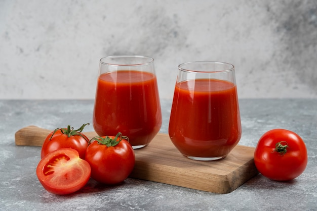 Two glass cups of tomato juice on a wooden board.