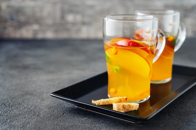 Two glass cups with apple tea on grey surface