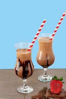 木の絶縁された青い背景にチョコレートミルクセーキと2つのガラスカップ