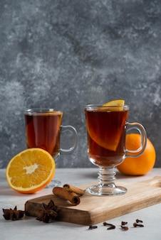 Две стеклянные чашки с горячим чаем и палочками корицы.