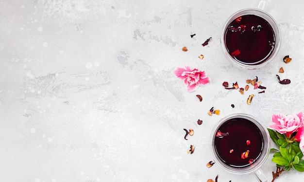 ピンクの花と乾燥茶葉と赤いホットハイビスカスティーの2つのガラスのコップ。トップビュー、コピースペース。