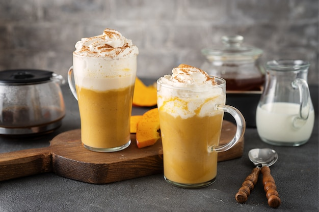 Two glass cups with spice pumpkin cappuccino on dark grey surface