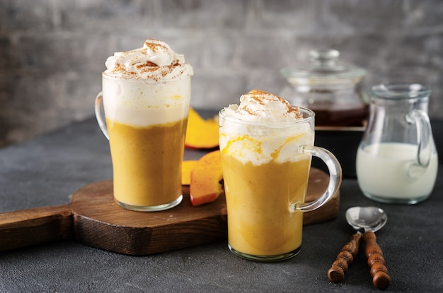 Two glass cups with spice pumpkin cappuccino on dark grey