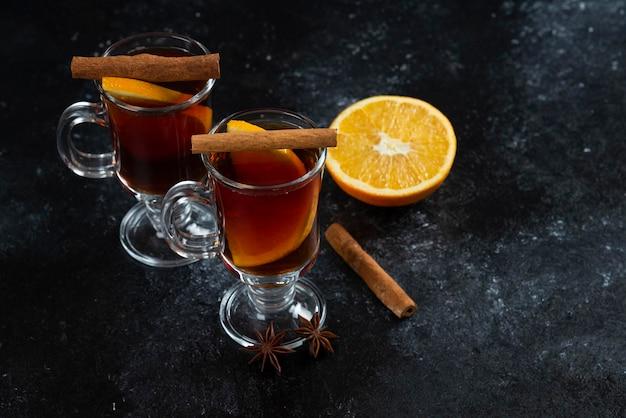 お茶とシナモンスティックが入った2つのガラスカップ。