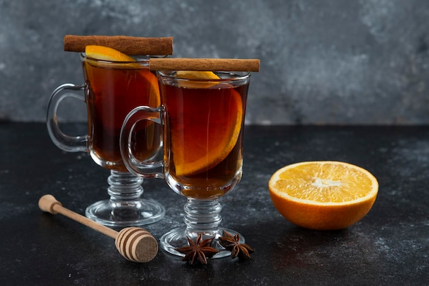 Two glass cups with yummy tea and cinnamon sticks.