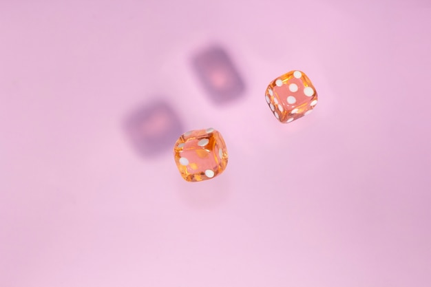 Two glass dice fall, bone to game on pink background.
