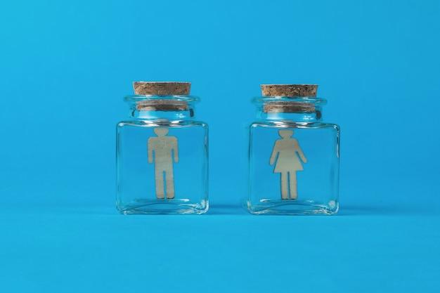 파란색 배경에 남성과 여성의 그림이 있는 두 개의 유리 플라스크.