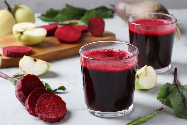 Two glass of fresh juice with beetroot and apples. chopped beet and apples on gray table. close up.