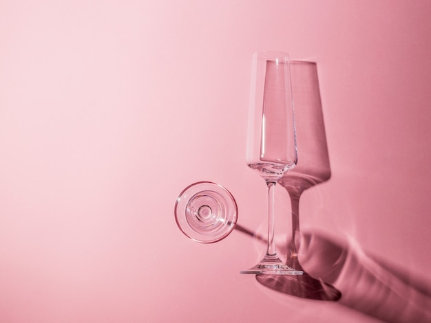 분홍색 배경에 하드 그림자와 함께 두 개의 유리 안경. 강한 빛의 유리 제품. 강한 빛의 유리 제품.