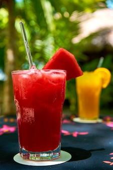 오렌지와 수박 주스의 상큼한 음료와 함께 두 개의 유리 잔.