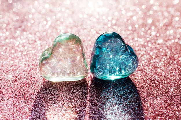 Two glass hearts, light green and blue on the blurry pink glitter background. lights shines through transparent hearts.
