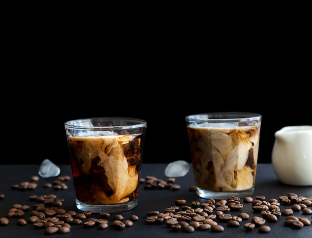 Two glass iced coffee with cream ice cubes and coffee beans on dark background with copy space