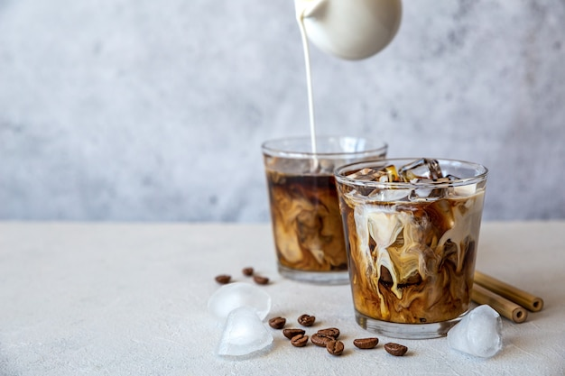 Two glass iced coffee with cream pouring from the top and coffee beans