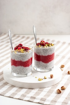 Two glass jar of chia pudding with raspberry, pistachio and red jam on a white table with striped tablecloth.