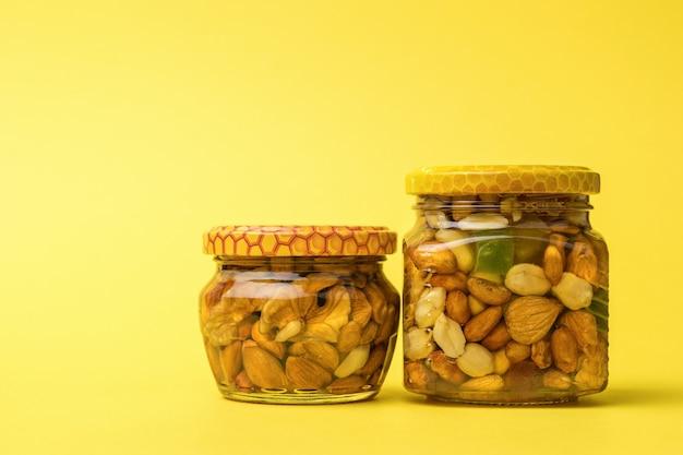 다양한 종류의 견과류와 꿀이 담긴 두 개의 유리병.