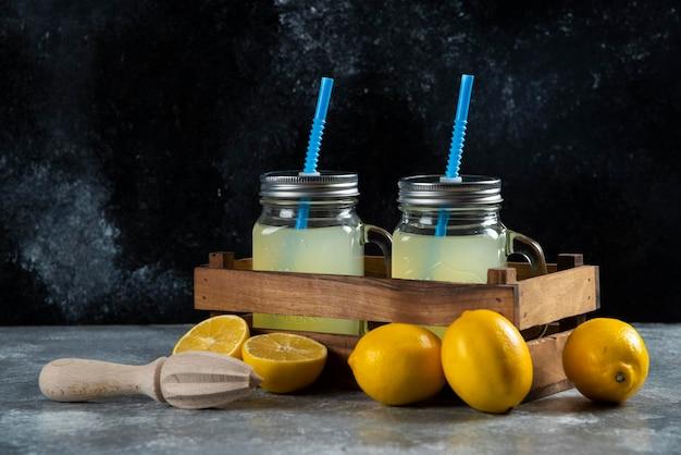 Due barattoli di vetro di succo di limone con cannucce e fette sul cestino di legno