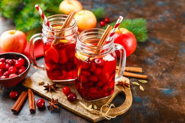 크랜베리로 만든 뜨거운 음료와 향신료, 멀드 와인, 펀치 또는 그 로그가 들어간 사과가 담긴 두 개의 유리 병.