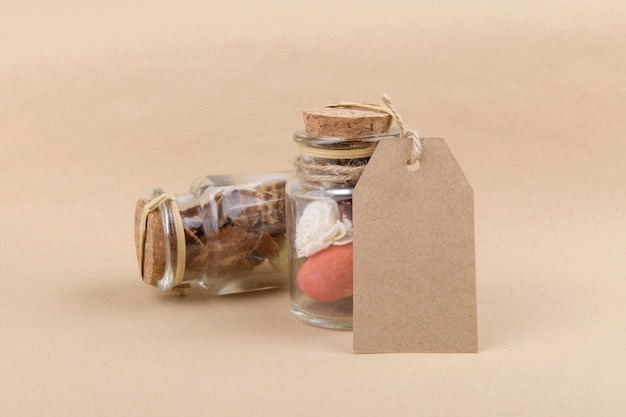 Two glass jars with dried herbs for aromatherapy with empty rectungolar tag on craft paper backrgound