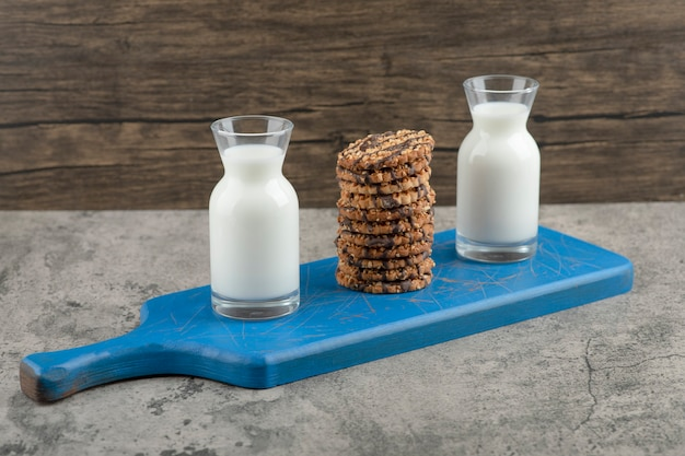 Two glass jugs of milk with oatmeal cookies on a blue wooden board.