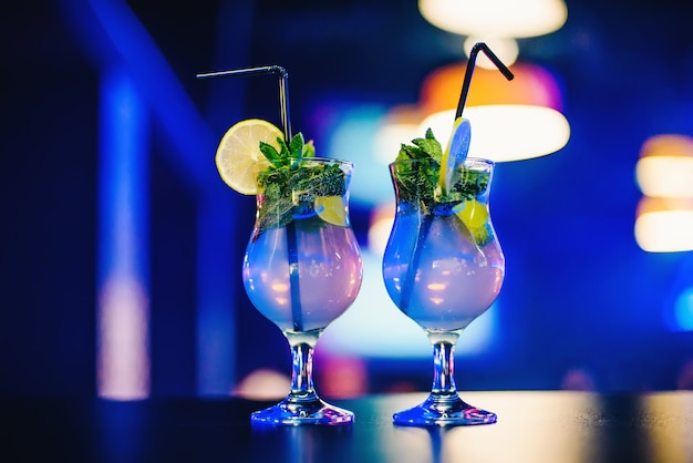 Two glass of mojito cocktail with straws lime and mint at the party