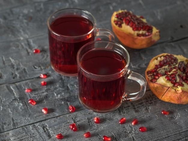 Две стеклянные кружки с гранатовым соком и свежими гранатами на деревянном столе. напиток полезен для здоровья.
