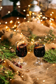 Two glass mugs of glint wine with fir branches