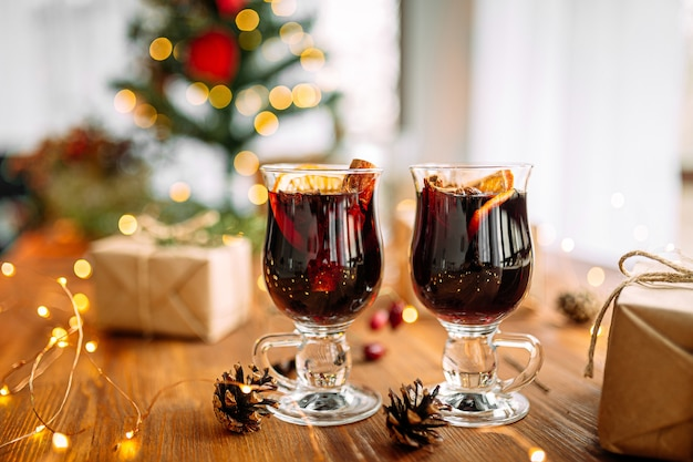 ぼやけた花輪ライトの背景を持つ木製のテーブルにグリントワインの2つのガラスのマグカップ