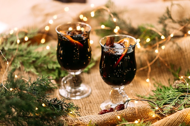 木製のテーブルにモミの枝と花輪のライトが付いたグリントワインの2つのガラスのマグカップ