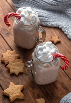 Two glass mugs with cocoa, marshmallows, sugar cane and ginger cookies on a wooden background.