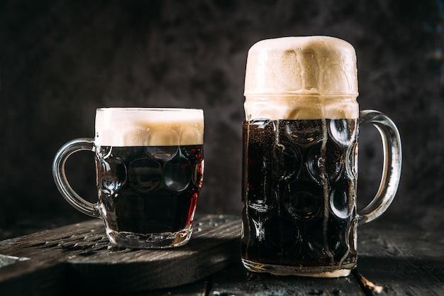Две стеклянные кружки с темным пивом на черном