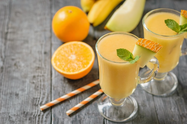 Two glass mugs with melon smoothie, orange and melon on a black wooden table.
