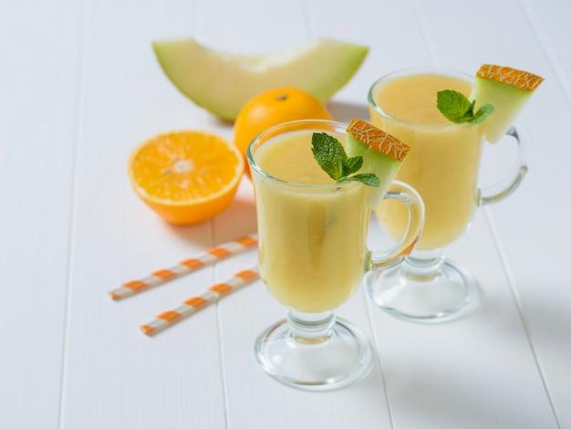 メロンのスムージー、オレンジ、白い木製のテーブルにメロンスライスの2つのガラスのマグカップ