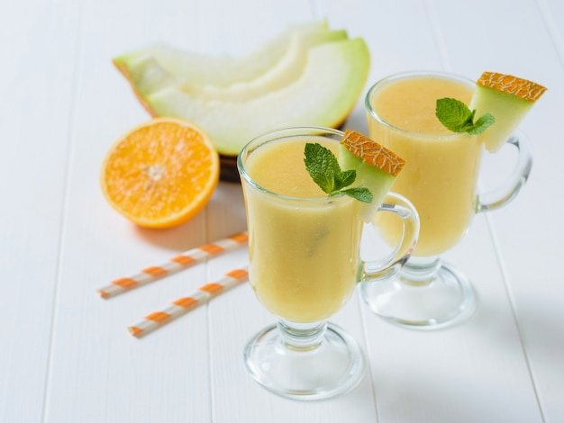 Two glass mugs with pieces of melon and mint on a white wooden table.